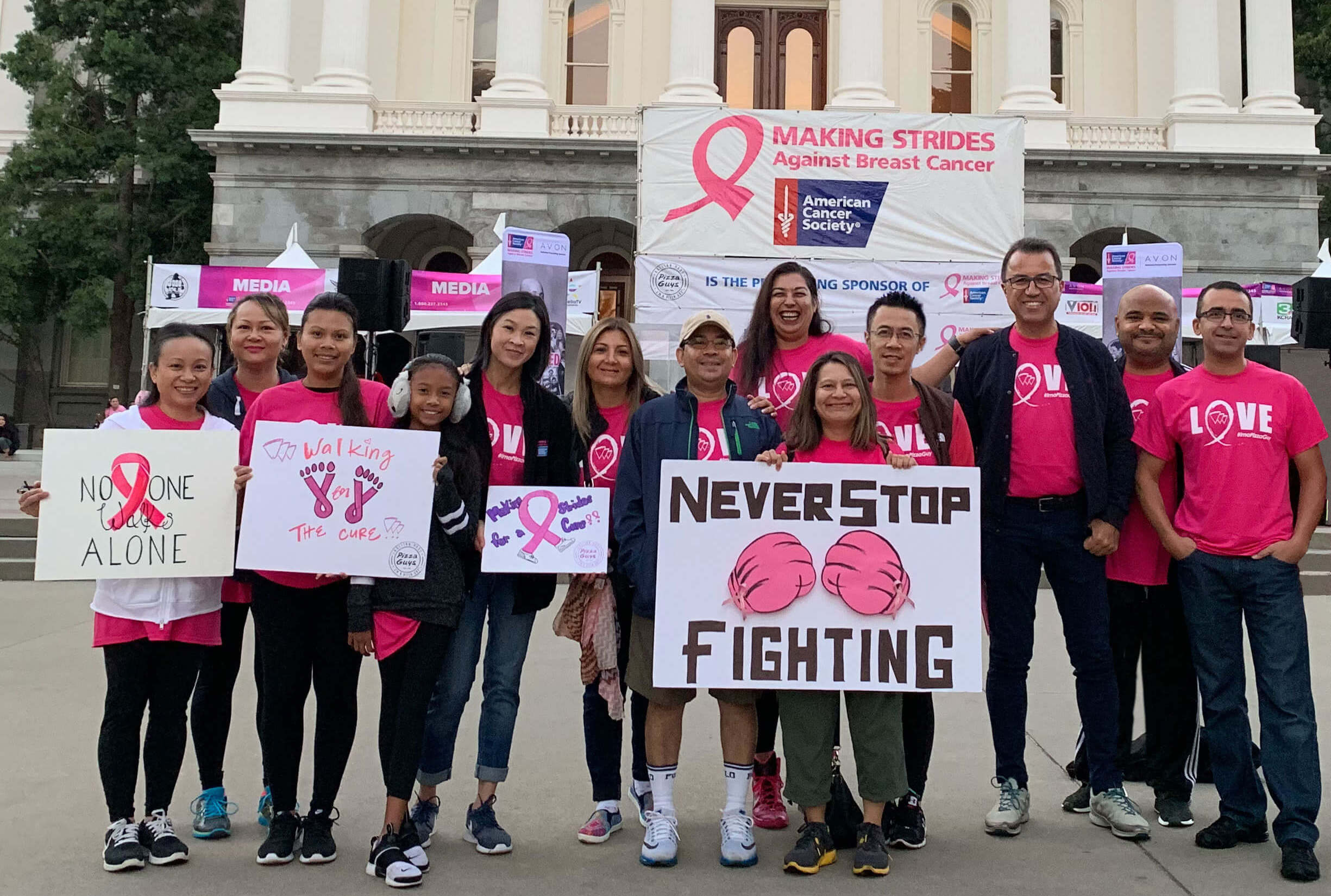 People standing in front of California Capital building for breast cancer awareness event.